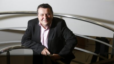 Richard Skellett stands on stairs, smiling