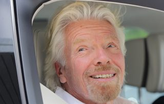 Richard Branson smiling smugly out of a car window