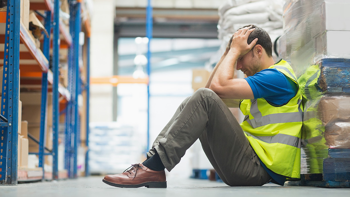 A warehouse worker sat down holding is head in his hands